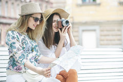 Beautiful girls tourists are looking for an address on the map sitting on the bench. They are wearing hats and smiling. Outdoors Stock Photography
