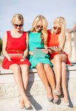 Beautiful girls toursits looking into tablet pcs Royalty Free Stock Photos
