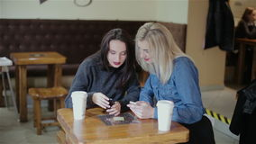 Beautiful girls view photos on the phone in a cafe. Two beautiful girls view photos on the phone in a cafe HD stock video footage