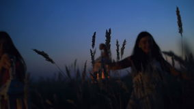 Beautiful girls walking in the field - in the hands holding candle lanterns stock video footage