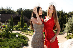 Beautiful girls wearing elegant dresses and luxurious crown Royalty Free Stock Images