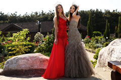 Beautiful girls wearing elegant dresses and luxurious crown Stock Photo