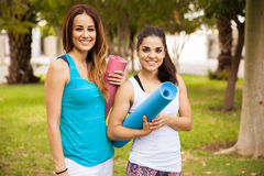Beautiful girls with yoga mats Royalty Free Stock Images