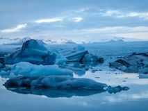 Iceland - Glacier lagoon with drifting icebergs and the glacier itself in the back. Beautiful glacier lagoon. Thousands of icebergs drifting lazily towards the royalty free stock photos