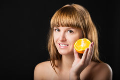 Beautiful glad girl and fresh juicy orange Stock Image