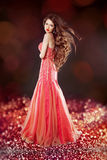 Beautiful glam with long hair posing in red dress over bokeh bri. Ght background Royalty Free Stock Photo