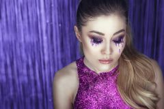 Beautiful glam model with artistic make up, glitter tears, wavy ponytail and top made of purple glitter posing against the tinsel. Close up portrait of a young Royalty Free Stock Photography