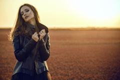 Beautiful glam model with long hair wearing black veiling dress and stylish leather jacket standing in the deserted field. Young beautiful glam model with long Stock Photos