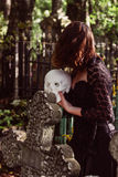 Beautiful glam rock style girl in black lingerie with fake skull head Royalty Free Stock Photo
