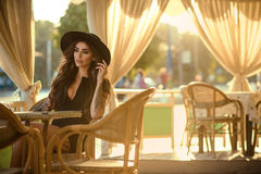 Beautiful glam tattooed brunette in little black dress and trendy fedora hat sitting in the nice open air summer restaurant. In the city at sunset and looking royalty free stock photography