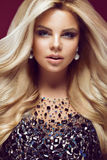 Beautiful glamor blondie woman in  elegant dress with jewels, evening makeup and curls. The beauty of the face. Stock Photos