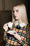 Beautiful glamor blondie woman in elegant jacket with evening makeup, sitting and drinking coffee or tea Stock Photography
