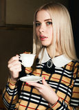Beautiful glamor blondie woman in elegant jacket with evening makeup, sitting and drinking coffee or tea Royalty Free Stock Photo