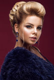 Beautiful glamor blondie woman in fur coat , evening makeup and hairstyle. The beauty of the face. Stock Photos
