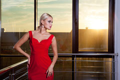 Beautiful glamorous blonde girl in a red dress posing near glass showcase in business center. Solar flare in the frame. Royalty Free Stock Photography