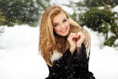 Beautiful glamorous girl in fur coat smiling in winter. Snowing Stock Images