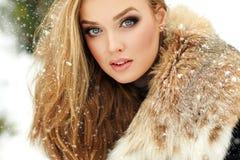 Beautiful glamorous girl in fur coat smiling in winter. Snowing Royalty Free Stock Photo