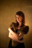Beautiful glamorous woman in fur coat posing at studio. Stock Photography