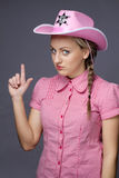 Beautiful glamour cowboy showing gun by fingers. On gray Stock Photo