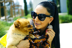 Beautiful glamour elegant brunette female model with a small dog. Portrait of beautiful glamour elegant brunette female model with a small dog Royalty Free Stock Photo