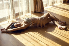 Beautiful glamour woman in luxurious dress lying on floor Royalty Free Stock Photos