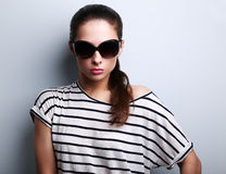 Beautiful glamour woman posing in fashion sunglasses on blue bac Royalty Free Stock Photos