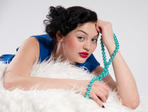 Beautiful glamour woman on white fur. Beads Stock Photo