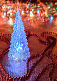 Beautiful glass Christmas tree on a background of lights.  Royalty Free Stock Photography