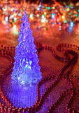 Beautiful glass Christmas tree on a background of lights.  Royalty Free Stock Photos