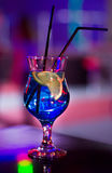 Beautiful glass with a cocktail at the bar on the table. Night club. Alcoholic drink blue color with a lemon on the inside Royalty Free Stock Photo