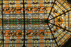 Beautiful glass mosaics in cathedral window. Orange figures created with glass royalty free stock image