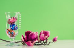 Beautiful glass vase with traditional painted Easter eggs and pearl necklace and a magnolia brach. Glass vase with colorful eggs and pearl nacklace and a Royalty Free Stock Photo