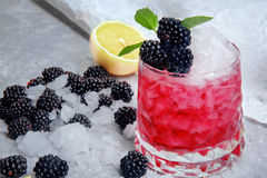 A beautiful glasses of alcoholic berry cocktails. A fancy shot with blackberries, mint and lemons on a white background. Stock Photo