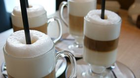 Beautiful glasses with coffee latte and big foam in the cafe on the table. Beautiful glasses with coffee latte and a big foam in the cafe on the table stock footage