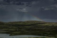 Beautiful gloomy dark stormy sky and rainbow over a green valley. Stock Photos