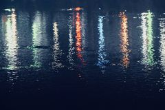 Colourful street lights reflection in water blurred photograph. Beautiful glowing street lights reflection in the lake water unique abstract blurred background Royalty Free Stock Photos