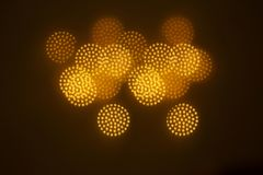 A beautiful gold bokeh with pattern of geometric elements on a dark background Royalty Free Stock Photo