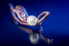 Beautiful gold brooch with pearl - reflection on blue background Stock Images