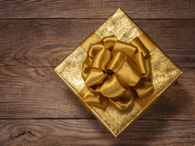 Beautiful gold gift box with a bow on the board Royalty Free Stock Images