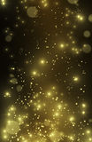 Beautiful gold glitter stars and star dust. Vertical festive glittering wallpaper, perfect for party invitation. Gold effect pixie dust on black. Bokeh golden Stock Photography