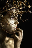 Beautiful Gold Painted Woman in Conceptual Beauty Themed Image Royalty Free Stock Photography