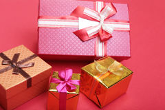 Beautiful gold present box with red bow and ribbons on backgound Stock Image