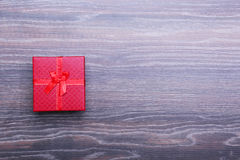 Beautiful gold present box with red bow and ribbons on backgound Royalty Free Stock Image