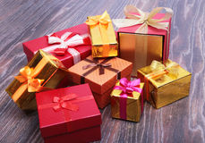 Beautiful gold present box with red bow and ribbons on backgound Royalty Free Stock Photography