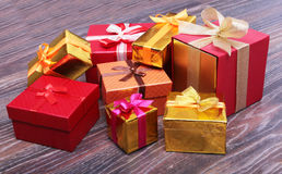 Beautiful gold present box with red bow and ribbons on backgound Stock Photos