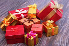 Beautiful gold present box with red bow and ribbons on backgound Royalty Free Stock Photo