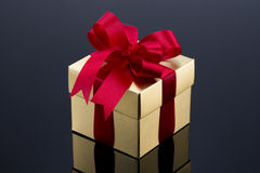 Beautiful gold present box with red bow and ribbons Stock Photos
