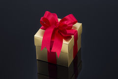 Beautiful gold present box with red bow and ribbons Stock Photo
