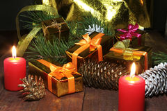 Beautiful gold present box with red bow, ribbons and candles on wooden background. Stock Image