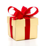 Beautiful gold present box with red bow and ribbons Royalty Free Stock Photography